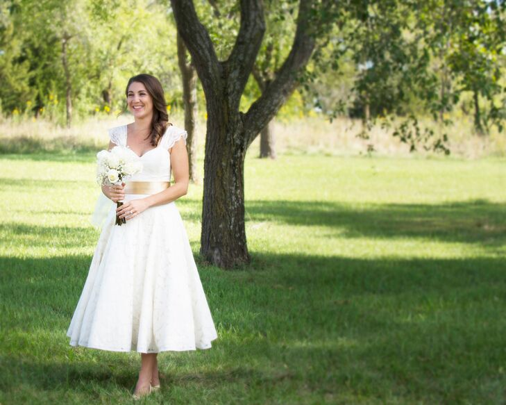 "Larrissa wore a tea-length A-line wedding dress. ""I had a tailor add lace sleeves and a gold belt to bring a bit of color, texture and coverage to my look,"" she says."