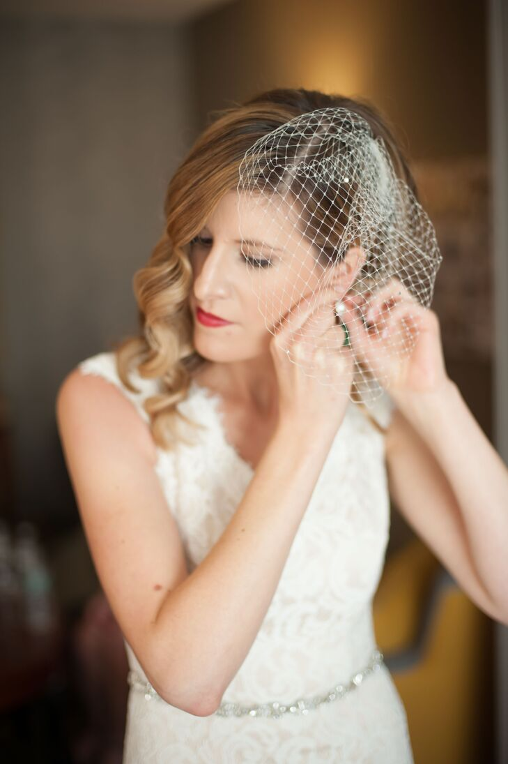 Megan wore a birdcage veil on her wedding day. She wore bright red lipstick and styled her hair in loose curls. She accessorized her wedding dress with a delicate crystal belt.