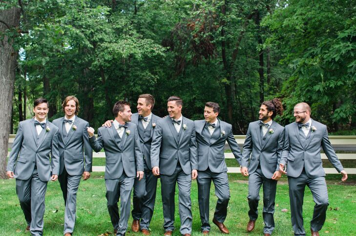 Groomsmen donned dark gray suits by Egara along with gray bow ties and brown leather shoes.