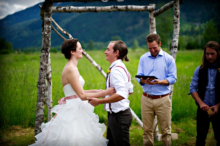 The couple exchanged vows outdoors, underneath a rustic branch arch, overlooking the gorgeous mountains of British Columbia.