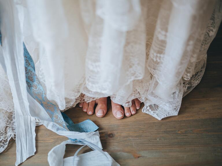 Bride's bare feet peeking out from under her lace dress on a wood floor