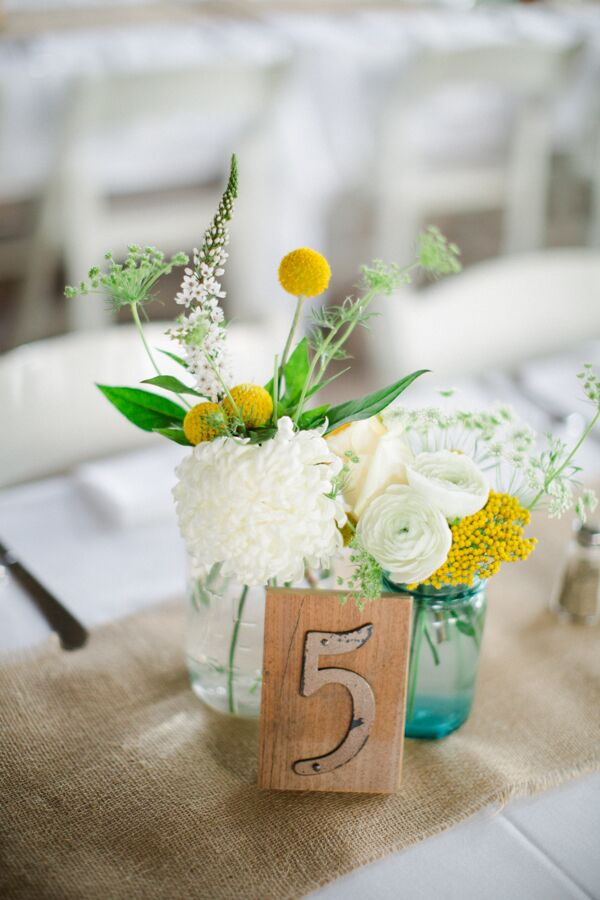 Yellow and white centerpiece with craspedia ranunculus