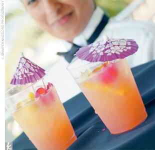 orange cocktail with a purple umbrella