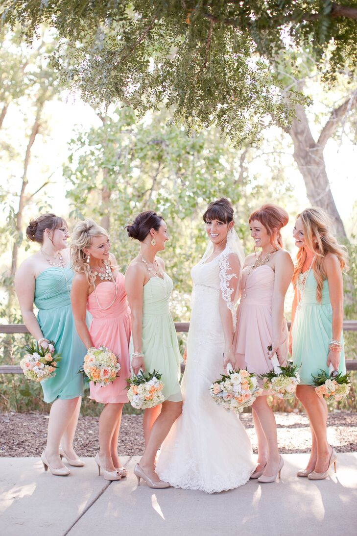 The bridesmaids wore custom cocktail-length strapless chiffon dresses from Dress Creative on Etsy. Each bridesmaid wore a different-colored pastel dress for a soft romantic flair. Wanting to add glamour to their look -- in honor of the 'Alice in Wonderland' theme -- they accessorized with multiple statement necklaces and bangle bracelets.