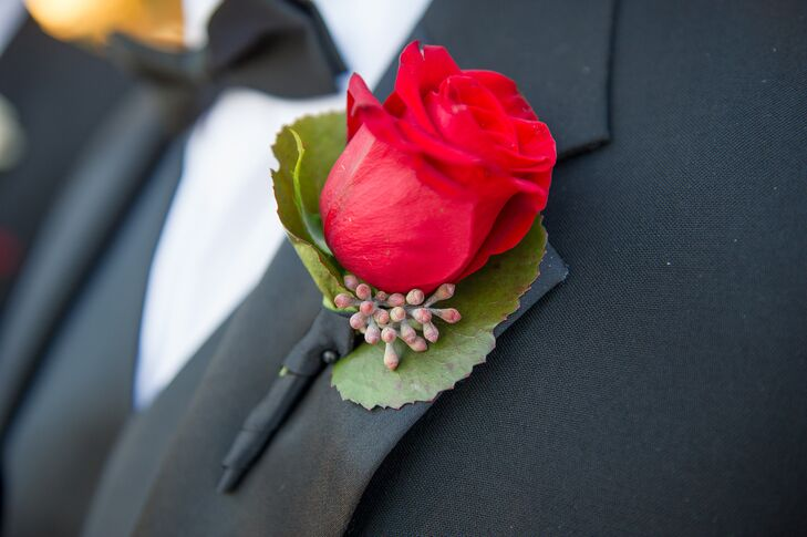 Each of Aaron's groomsmen wore a red rose boutonniere on his classic black tuxedo. Aaron stood out among them with a white calla lily boutonniere, red paisley bow tie and matching vest.