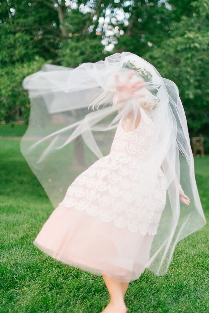 The flower girl wore a blush tulle knee-length dress decorated with lace applique for the ultra-chic garden-party wedding. Bryn and Ben loved how it matched the wedding party and the palette. She completed her look with a boho flower crown.