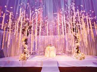 Indoor wedding ceremony with purple uplighting and flower garlands