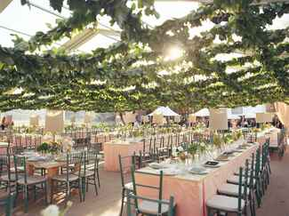Wedding reception tent with a grid ceiling of lemon leaf garland