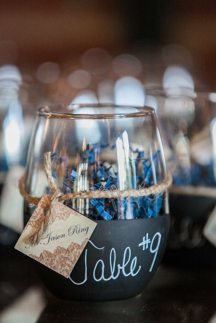 Each escort card was wrapped around a wine glass painted with chalkboard paint displaying a table number.