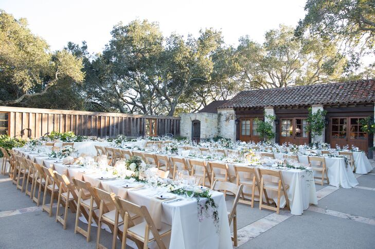 At the outdoor reception, long tables dressed in white tablecloths were lined with wooden folding chairs. The tables were draped with long green vines draping down the middle, just like a runner. Lush centerpieces of roses accented with eucalyptus and leaves decorated the middle.
