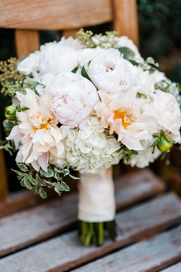 Laura's romantic bouquet included a mix of café au lait roses, dahlias and peonies and was wrapped with the lace cap that Daniel wore home from the hospital.