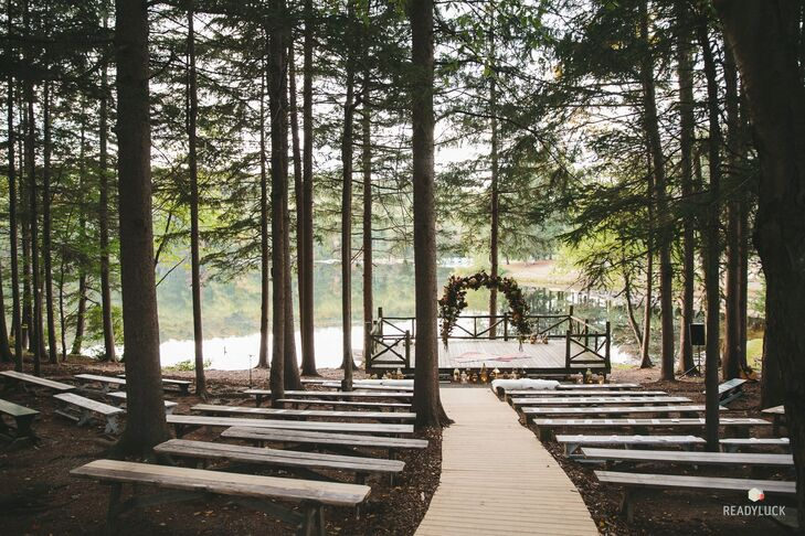 "Amy and Geoff's ceremony was held outdoors, cloistered in the woods with a lake as the backdrop at Cedar Lakes Estate in Port Jervis, New York. ""Since I'm used to shooting TV, I timed the ceremony with the sunset so that the lake would be gleaming as we stood before everyone,"" Amy says. The ceremony site was simply decorated with an arch of greenery and flowers."