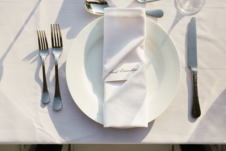 Simple calligraphed place cards were tucked into white linen napkins.