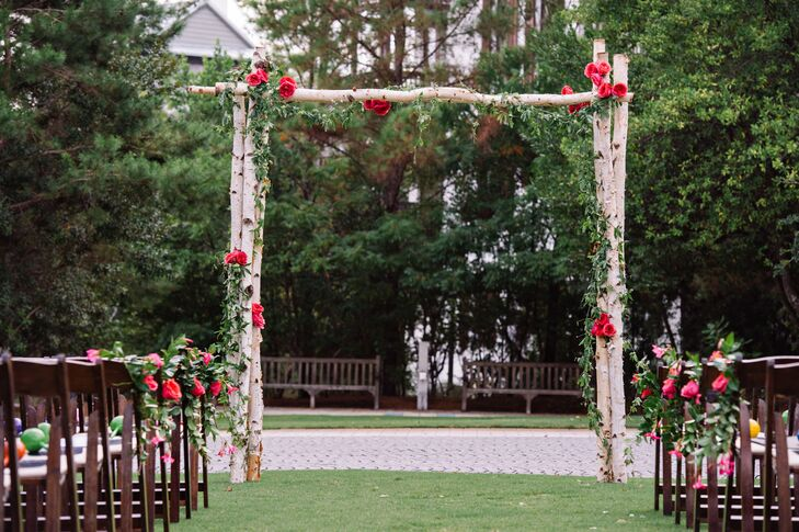 Their wedding arch captured the natural setting at St. Augustine Green with an understated design. Events by Nouveau, the couple's florist, decorated each birch-wood post with a grand garland of greenery and bunches of fuchsia garden roses, which also accented the aisle.