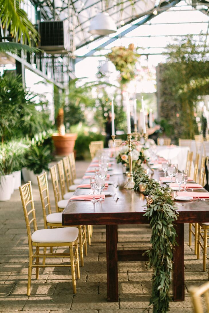 The wedding party sat at a wooden farm table decorated with a seeded eucalyptus runner, a golden urn holding a floral arrangement and golden candelabras.
