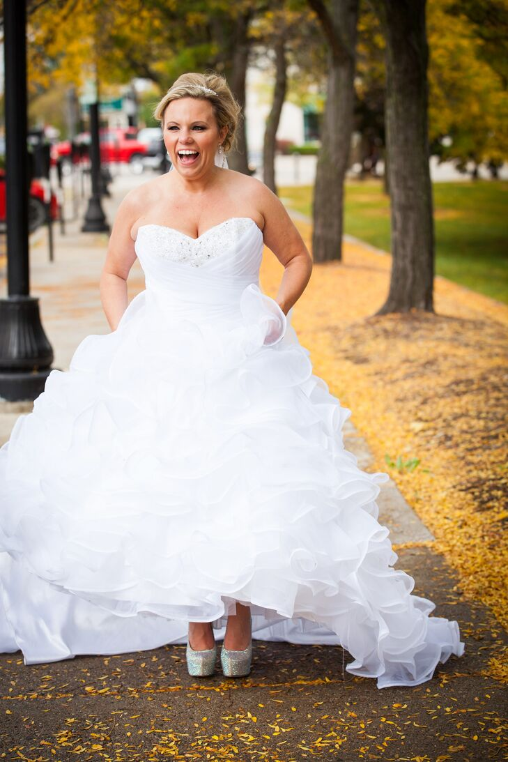For her fall wedding, Tiffany wore a strapless, drop waist wedding gown by Mori Lee with a frilly tulle skirt. Although the full skirt looks heavy, Tiffany assures that it was incredibly lightweight and easy to move it.