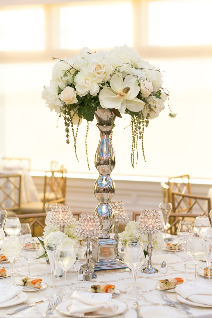Tall arrangements of white orchids, roses and hanging amaranthus topped the round tables at the reception.