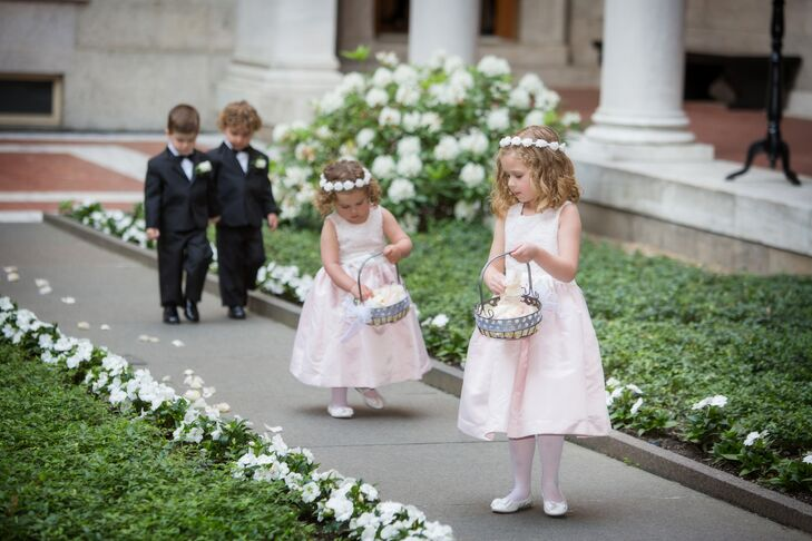 The couple's two flower girls wore light pink and ivory satin dresses by US Angels. The girls carried baskets of pink rose petals which they scattered across the ceremony aisle.
