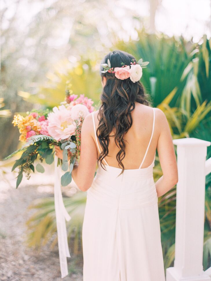 "The plan was for stylists at Blo Blow Dry Bar to put her hair into a braid and beachy curls with a flower crown, but things changed the morning of her wedding. Instead of hiding her braid with the arrangement, her florist and hairstylists helped weave the flowers directly into her hair. ""The result was gorgeous,"" Francesca says. She loved how the pink garden rose, white ranunculus, eucalyptus and red hypericum berries all tied into the half-up bridal hairstyle."
