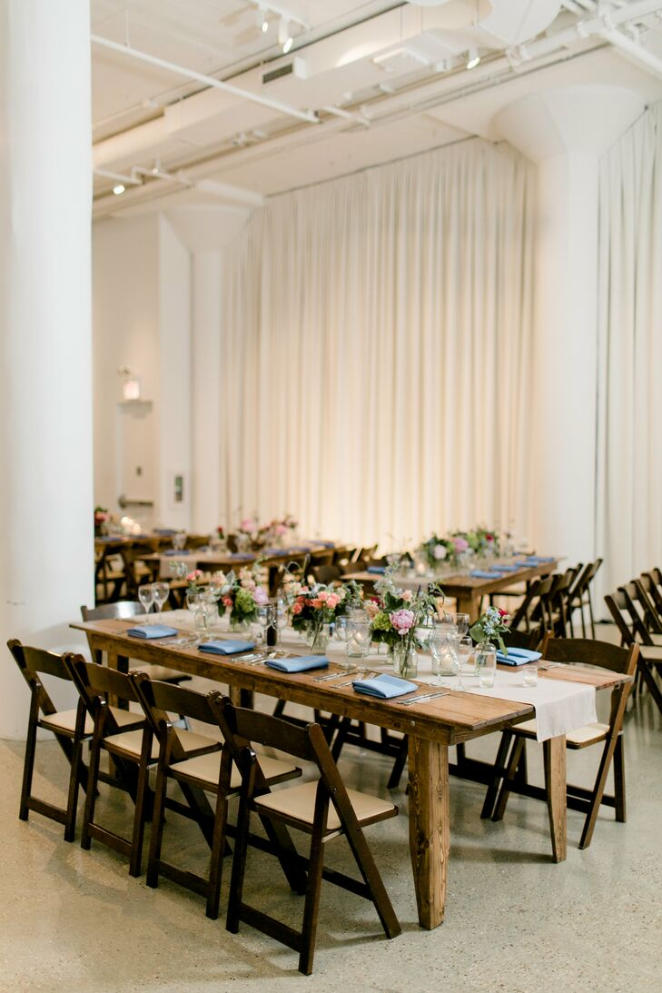 Wooden tables, taupe runners (rather than linens), candles and local and naturally sourced floral arrangements created a sophisticated yet rustic vibe at Chez in Chicago, Illinois. Three types of centerpieces provided some variety: a single large arrangement in a wooden box flanked by pillar candles, a branch surrounded by flower clusters in small vases and three smaller arrangements in glass mason jars with flower clusters in small vases. The tablescapes were further accented with tealights.