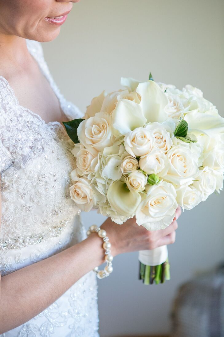 The bride held an ivory bouquet of ivory vendela roses, white mini calla lilies, white hydrangea and ivory sprayrnroses accented with foliage. The bouquet was designed by Tanjeeryn Designs.