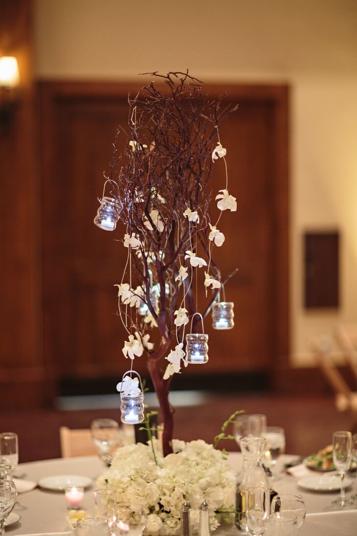 Candles and white-flower garland hung from small branches to create romantic garden centerpieces.