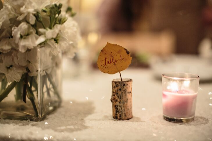 Small leaves stuck into wooden corks served as rustic table numbers.