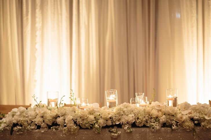 The sweetheart table was decorated with floating candles and a white-flower garland.