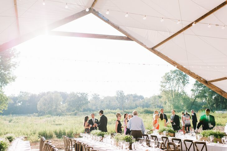 The bride's father built a smaller tent attached to the main tent for guests to enjoy a casual cocktail hour on the property, where they were able to walk down to the pond of sit along benches lining the space,