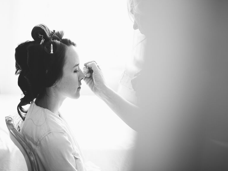 Bride getting makeup done before wedding