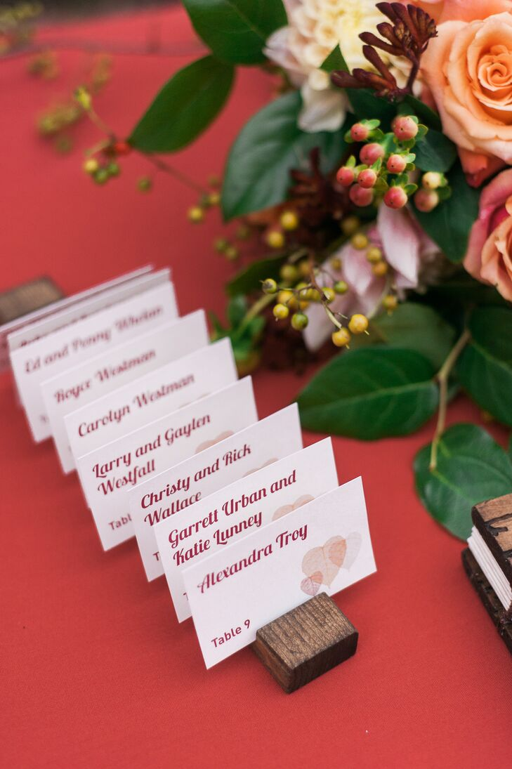 John's sister created the white escort cards with burgundy text, decorated with heart-shaped watercolor designs that added a romantic touch. Wooden slabs with slits displayed the paper cards for guests to easily locate.