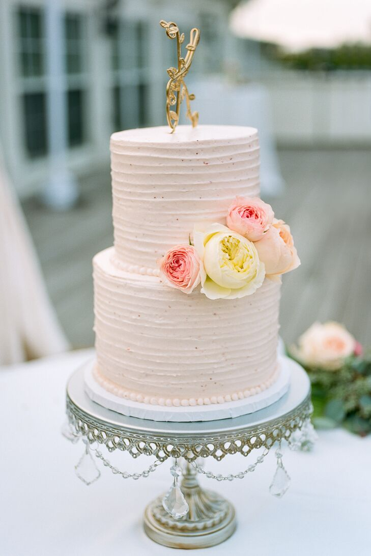 Katie and Nick's wedding cake featured two blush tiers to complement Katie's wedding dress with fresh ivory and blush garden rose accents and a gold, twisted metal 'K' cake topper.