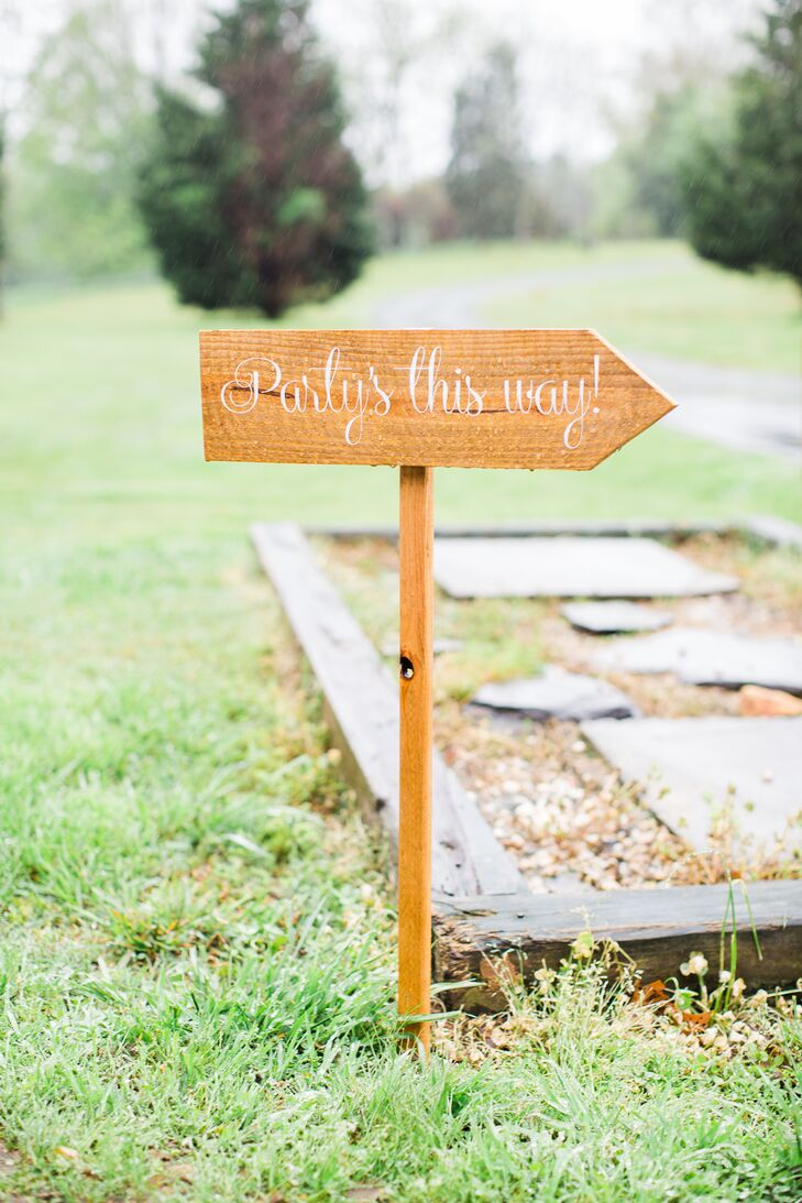 "The grounds of the Barn at Valhalla in Chapel Hill, North Carolina, were decorated with some rustic signs to let guests know where to go. All the signs were modern unfinished wooden arrows that said things such as ""Party's This Way."""