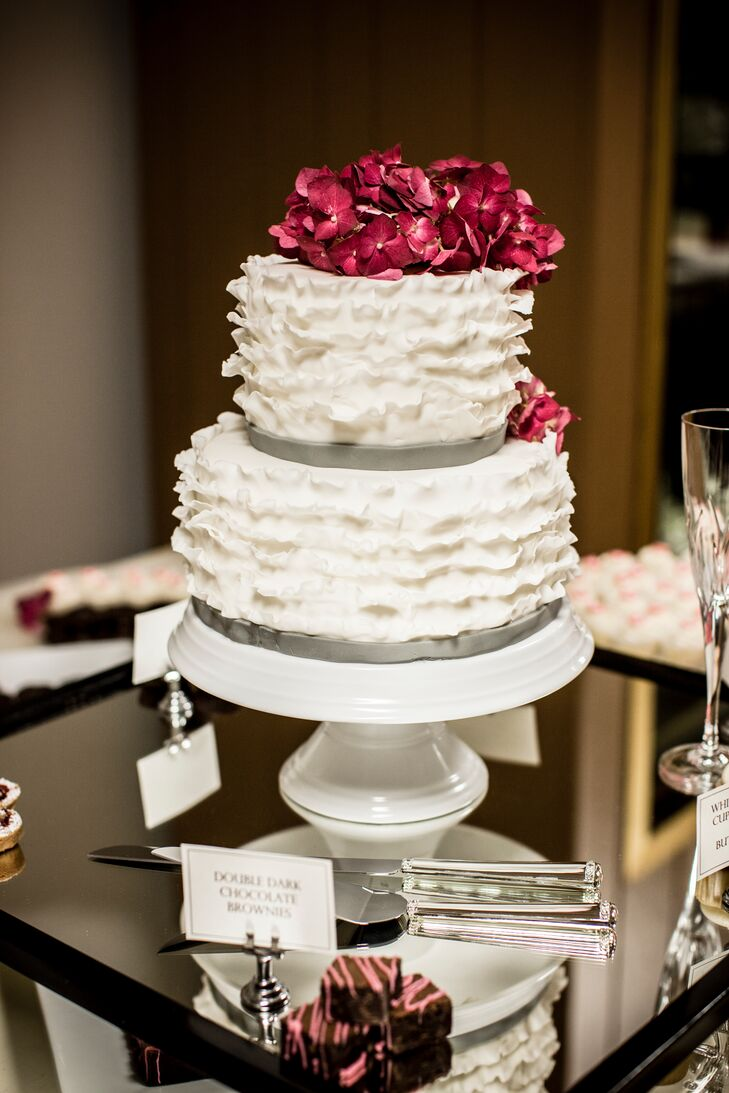 The couple enjoyed a two-tier cake decorated with ruffled buttercream and topped with burgundy hydrangeas.