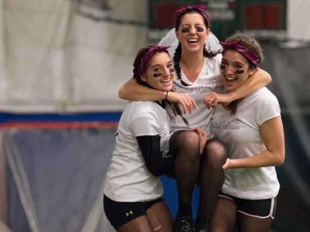 Team Bridal Warriors carries their bride-to-be to the finish line of an obstacle course at Bridal Wars