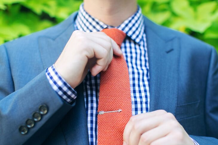 Ron wanted his ensemble to express his personality and decided on a less traditional suit from J.Crew. A navy gingham shirt was paired with the heathered navy suit along with an orange knit tie and arrow tie bar.