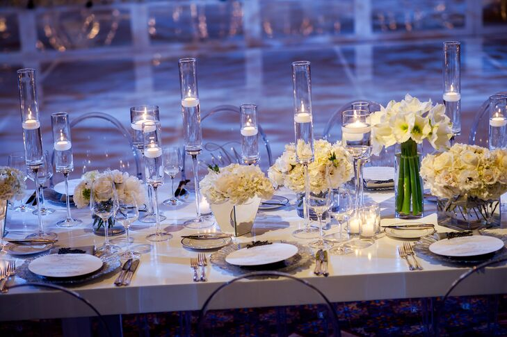 """Since the wedding took place in December, I decided on a modern icy winter wonderland theme,"" Shelby says. Clear chairs, white beaded linens and an abundant array of white orchids and peonies with metallic charcoal fabric drapery created a cool modern atmosphere of winter glam."