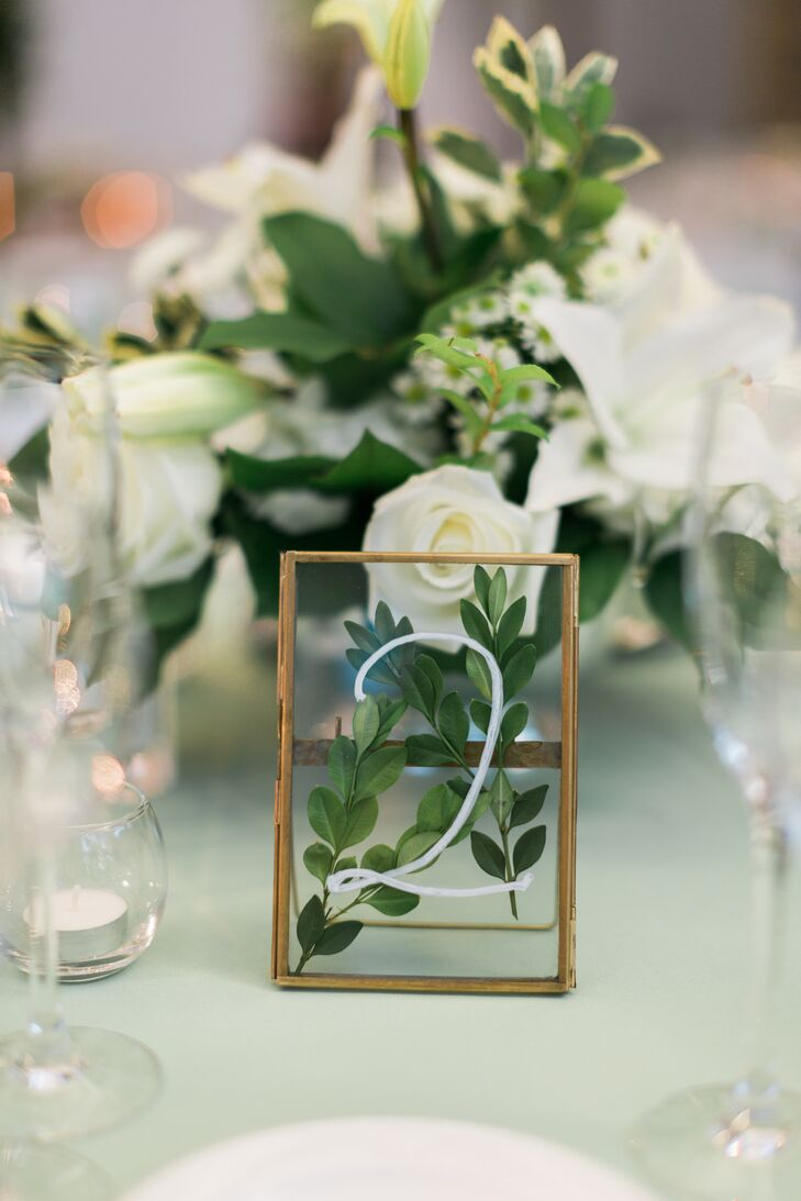 Table numbers featured pressed greens in a simple gold frame.