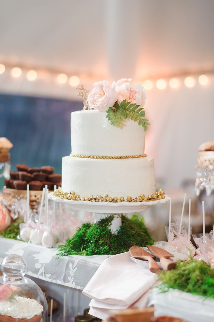 Erica and Cole chose a simple two-tier buttercream frosted vanilla cake by show Me Love Pops for the reception. It was topped with two gold deer and blush garden roses. Gold berries or a gold rope design was placed at the base of either tier. The cake was surrounded by a grand assortment of desserts and placed atop a white vintage piano.