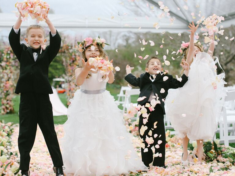 Ring bearers and flower girls throwing rose petals