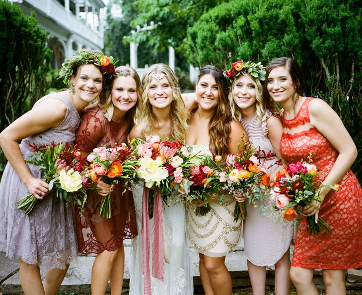 Each of Gina's bridesmaids stood out with a different look. Based on a muted berry and rust-inspired color scheme, they sported knee-length lace, beaded and sheer dresses. The women also chose their own hairstyles and neutral shoes. Gina simply tied their looks together with lush garden-style bouquets from Belovely Floral and Event Design and two flower crowns. Each arrangement had a series of pink garden roses, greenery, eucalyptus and orange poppies.