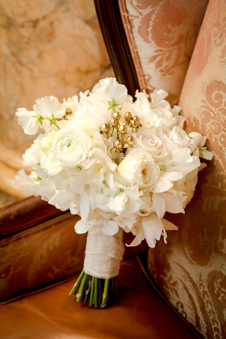 Beth carried a bouquet with white ranunculus, white roses, and other white seasonal flowers. Her bouquet also had little gold bells so that it jingled when she walked, which fit the winter wedding theme.