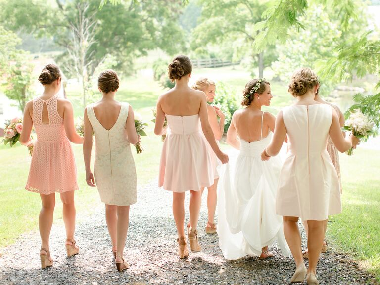 Bridesmaids in neutral and blush cocktail dresses walking with a bride in a floral crown.