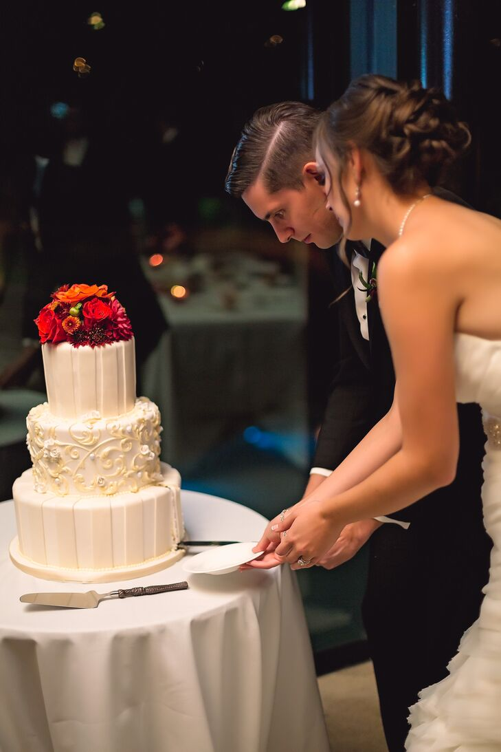 The couple cut into their three-tier white cake by Dessert Trends. Fresh and bright orange and red flowers decorated the top layer of the cake.