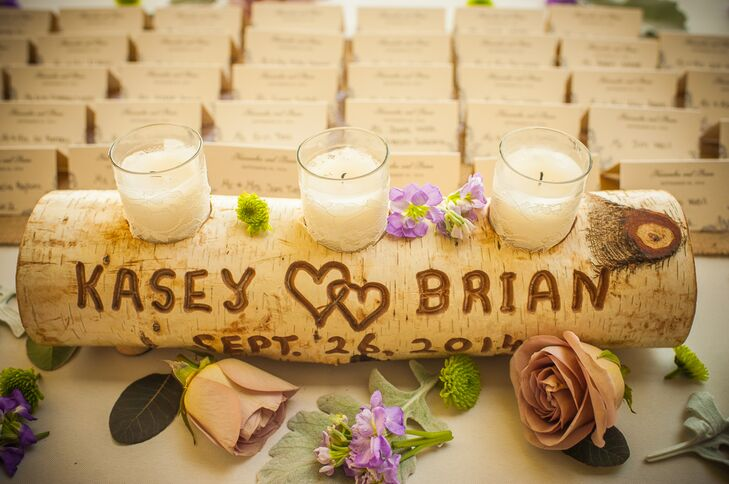 The escort card table was decorated with a wooden log engraved with the couple's names and wedding date. Placeholders were cut into the log to hold votive candles. Scattered throughout the table were green mums, lavender roses and purple stock flowers.