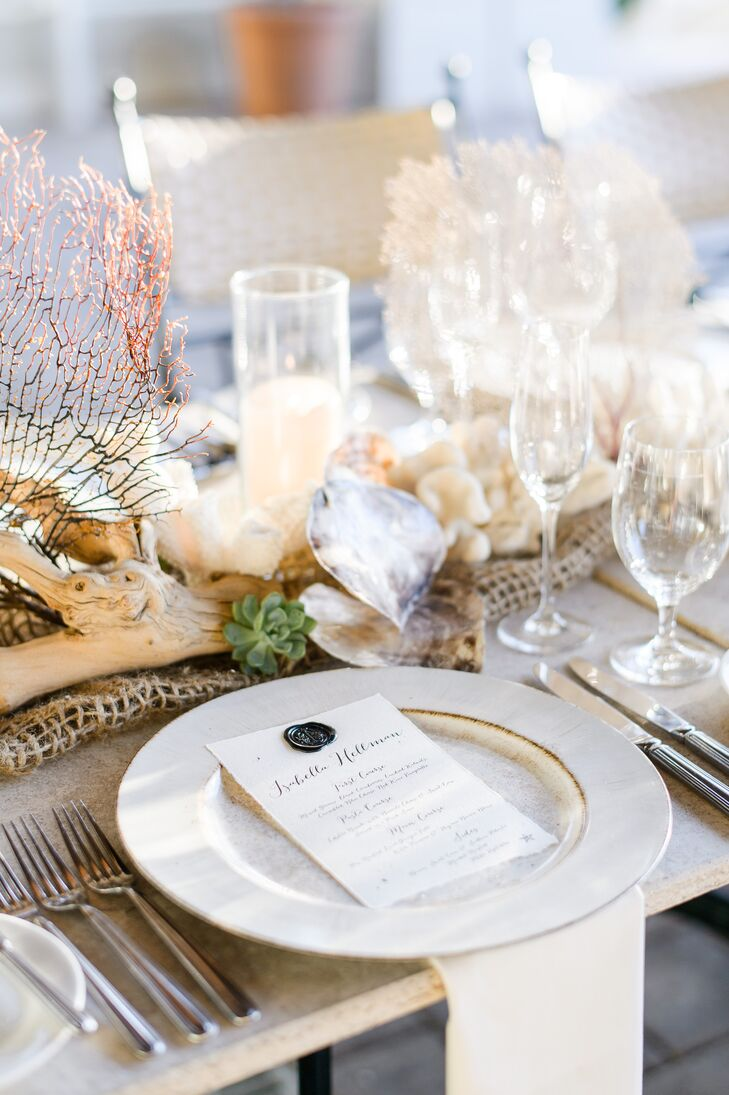 "While the centerpieces fully embodied the beach-chic theme, the place settings themselves took on a more understated tone. Antiqued white dinnerware and linens gave way to hand-lettered menu cards bearing the names of each guest and a wax ""T"" seal."