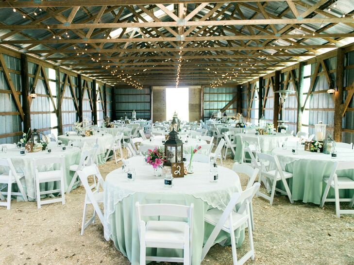 The reception took place in a recently refurbished barn with exposed beams on the farm property. Ashley and Brad used string lights, white linens, and white seating to transform the rustic space into a romantic dining and dancing experience.