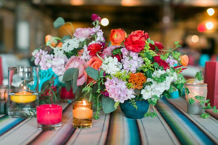 arranjo de mesa baixo, com flores coloridas e velas na mesa