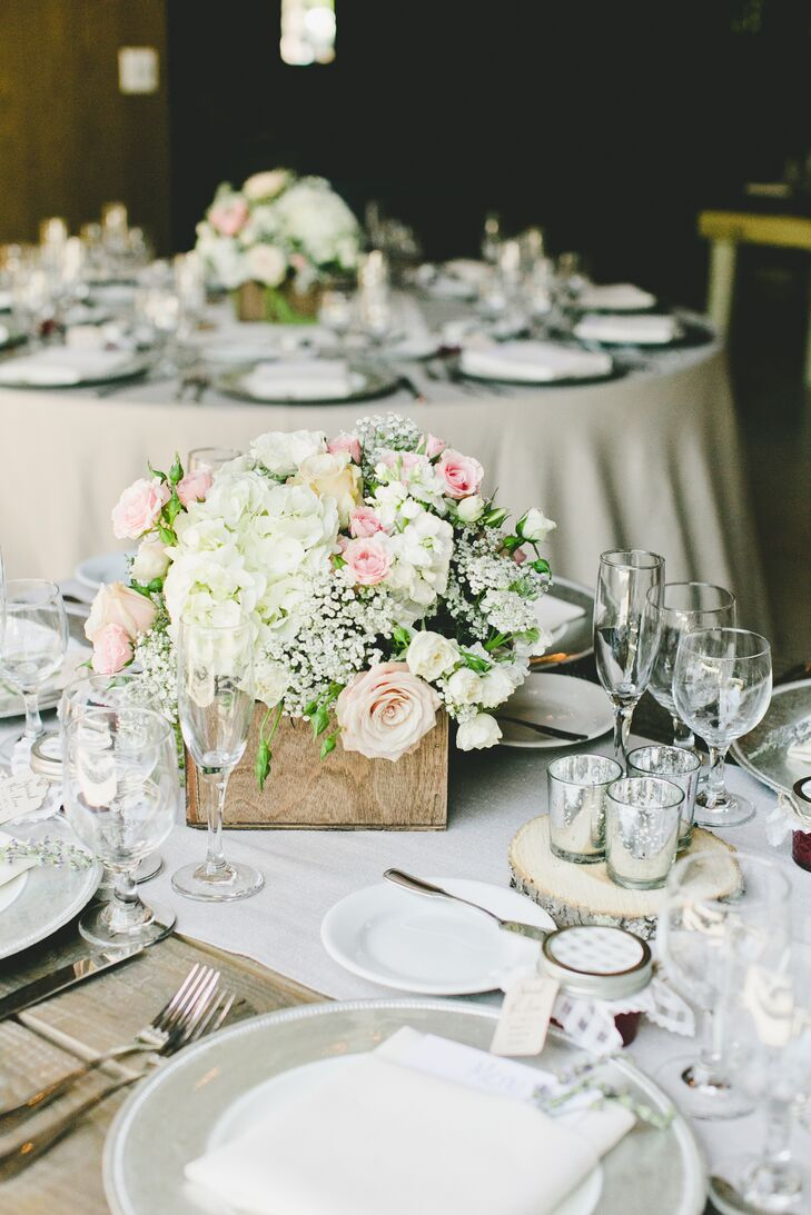 Rustic boxes filled with ivory and pink blooms—ranging from hydrangeas to roses and baby's breath—sat on top of white runners and decorated dining tables.