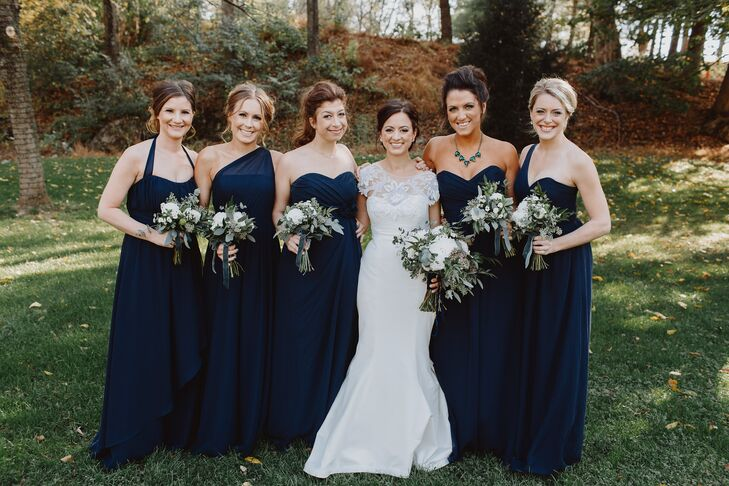To create a cohesive, elegant, but not at all stuffy look for her bridesmaids, Shannon had all five of the girls choose a navy, floor-length gown in a style they loved from Alfred Angelo's bridesmaid collection. They paired the gowns with jewelry and shoes of their choice and opted for makeup in warm gold tones at Shannon's request. To set her maid of honor apart from the rest, Shannon gifted her a statement necklace with gold and emerald accents.